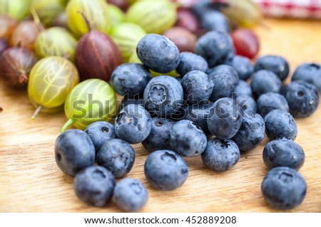 Fresh blueberry and gooseberry on the wooden table - food picture - stock photo