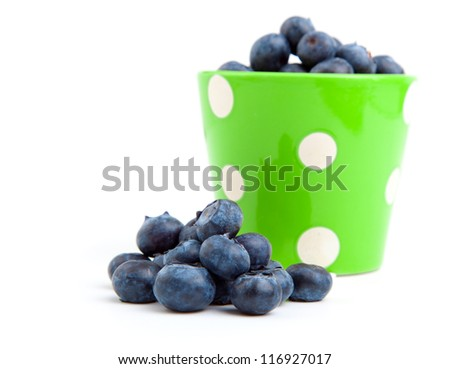 fresh blueberry in a green mug over a white background.