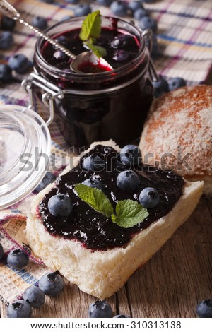 Fresh blueberry marmalade and sweet bun close-up on the table. Vertical - stock photo