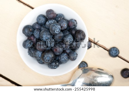fresh blueberry on a bowl with silver spoon over wood table - stock photo