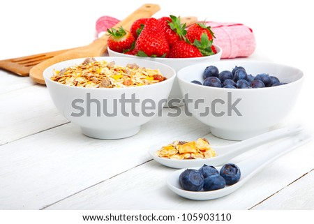 fresh blueberry, strawberry and corn flakes in white porcelain bowl, wooden table