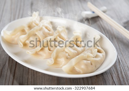 Fresh boiled dumpling on plate. Chinese food with hot steams on old wooden background.  - stock photo