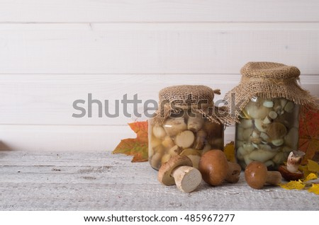 Fresh boletus and glass jar with preserved mushrooms