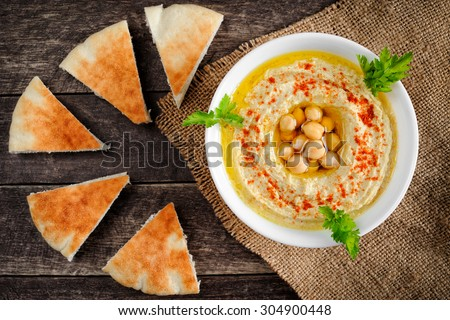 Fresh bowl of homemade hummus with chickpeas, olive oil and parsley. Served with pita bread - stock photo