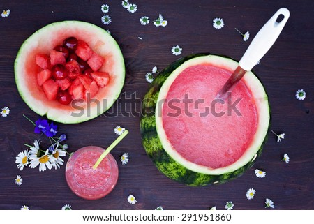 Fresh bowl of watermelon drink, drink in a glass and some fresh fruits on a brown wooden table background, daisy flowers on the table - stock photo