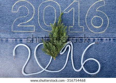 Fresh branch of christmas tree and the numbers 2016 of rope and chalk contour on the background of the jeans. Christmas theme. - stock photo