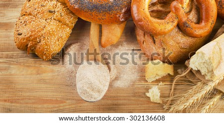 Fresh bread and flour on  rustic wooden background. Top view