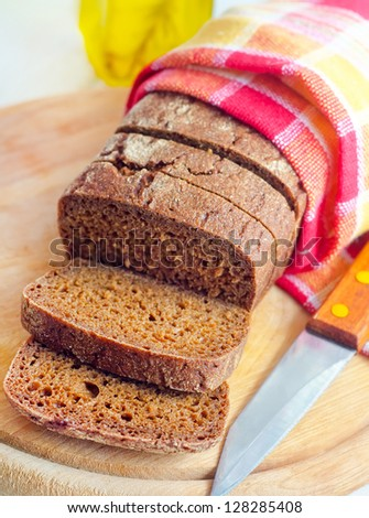 Fresh bread and knife on the wooden board - stock photo