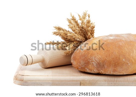 Fresh bread and wheat ears on a wooden board isolated on white background.