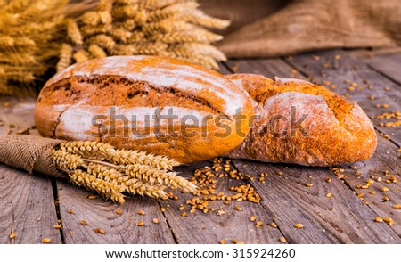 fresh bread and wheat on the wooden - stock photo