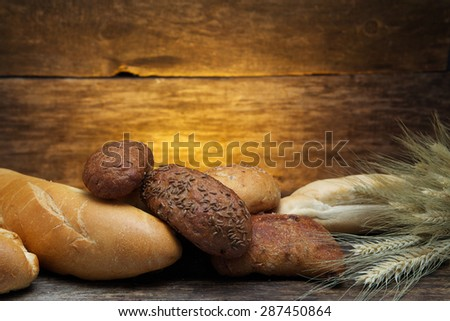 fresh bread  and wheat on the wooden background - stock photo
