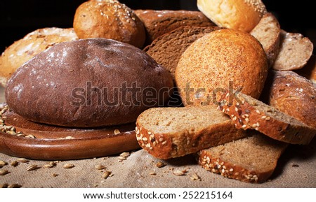 Fresh bread and wheat on the wooden table. - stock photo