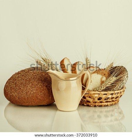 Fresh bread and wheat on the wooden table. Food background - stock photo
