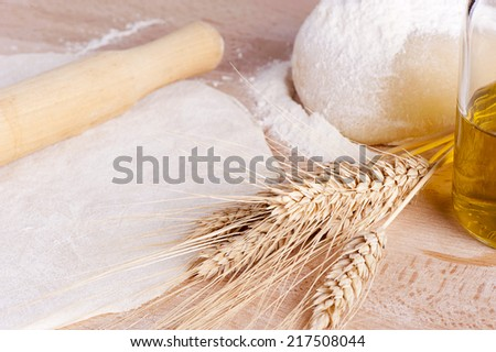Fresh bread dough with a rolling pin on a wooden table  - stock photo