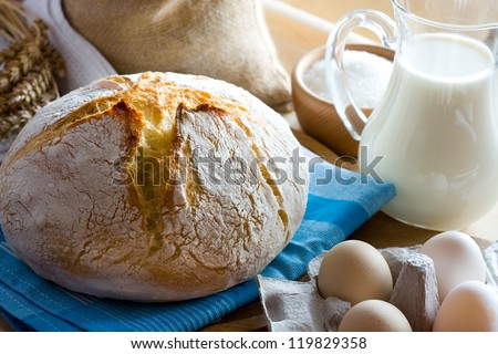 Fresh bread, glass jug with milk and eggs - stock photo