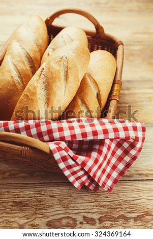 Fresh bread in  basket on a wooden table  - stock photo