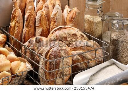 Fresh bread in metal basket in bakery on wooden background - stock photo