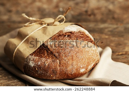 Fresh bread on old wooden table - stock photo