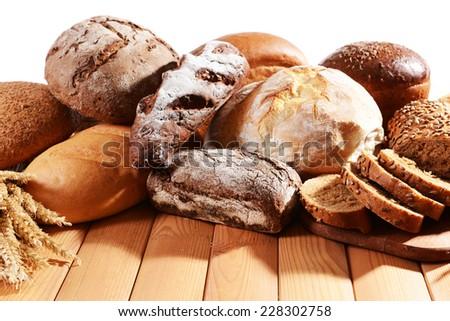 Fresh bread on table on white background - stock photo