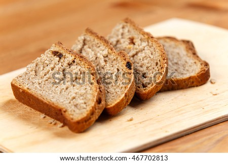 Fresh bread slices on rustic wooden board