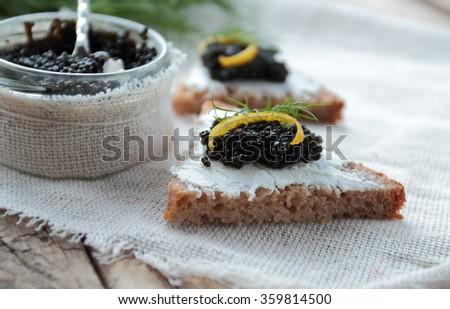 Fresh bread with black caviar and cream cheese - stock photo