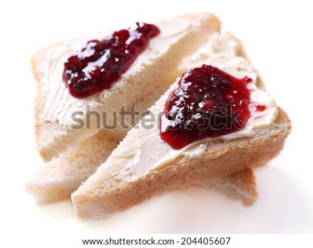 Fresh bread with blackcurrant jam and homemade butter, isolated on white