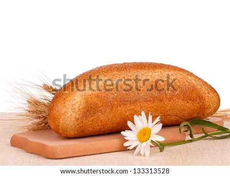 Fresh bread with bran on a cutting board on burlap over white background - stock photo