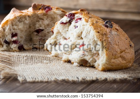 Fresh bread with cranberries on a wooden background.