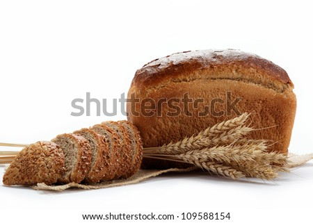 Fresh bread with ears of wheat on the canvas. - stock photo
