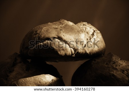 Fresh bread with raisins on red background. Contrast light and dark shadows. Sepia aged photo.  - stock photo