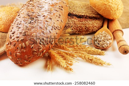 Fresh bread with wheat and wooden spoon of sunflower seeds, closeup - stock photo