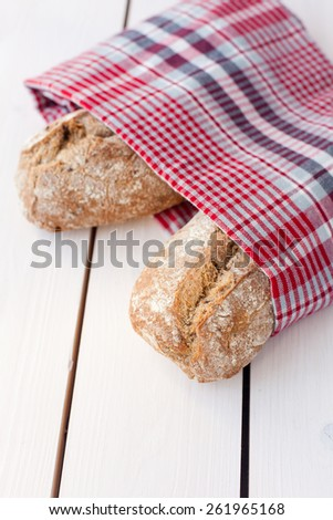 fresh bread wrapped in a towel - stock photo