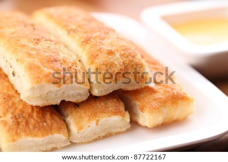 Fresh breadsticks served with dip sauce. - stock photo