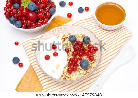 fresh breakfast - muesli with berries, yogurt, honey, top view - stock photo