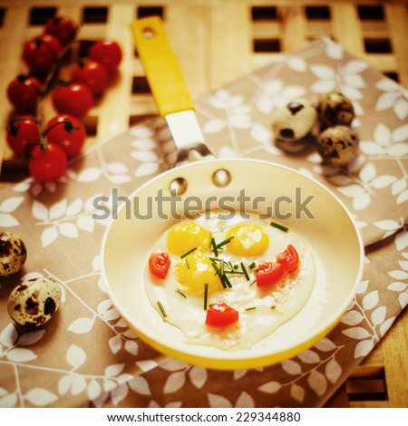 Fresh Breakfast with fried eggs pan. Quail eggs in little yellow frying pan, cherry tomatoes served on wooden table. Top view. Instagram color effect. - stock photo