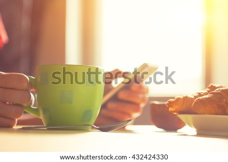 fresh breakfast with hot coffee and browsing smartphone in morning sunlight - stock photo