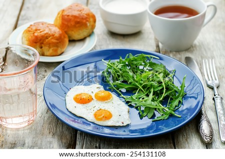 fresh breakfast with scrambled eggs and arugula on a white wood background. tinting. selective focus - stock photo