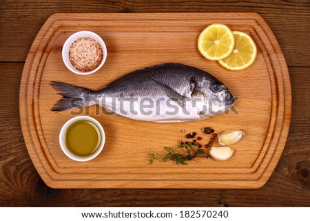 Fresh bream fish on cutting board with ingredients, top view - stock photo