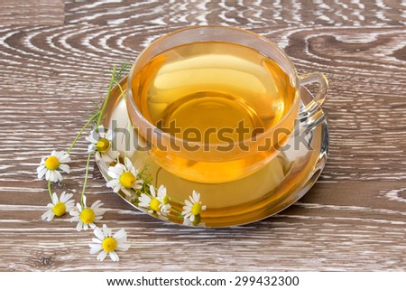 Fresh brewed chamomile tea in a tea cup with chamomile blooms - stock photo
