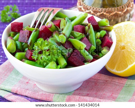 Fresh bright salad with green bean-pods and roasted beetroot with sunflower seeds in white bowl - stock photo