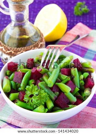 Fresh bright salad with green bean-pods and roasted beetroot with sunflower seeds in white bowl