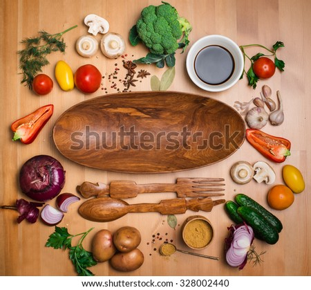 Fresh broccoli and vegetables ingredients for tasty vegetarian cooking on rustic wooden background around wooden salad plate, top view. Healthy eating, diet or vegan food concept. - stock photo
