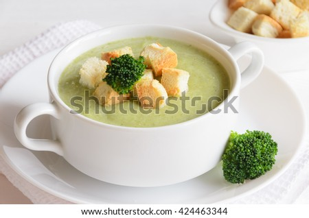Fresh broccoli cream soup in bowl served with croutons on white background. Selective focus - stock photo