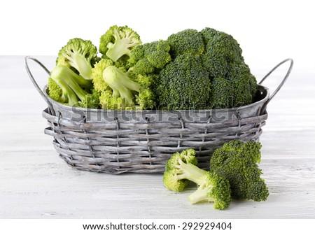 Fresh broccoli in basket on light background - stock photo