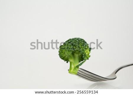 Fresh broccoli on fork - stock photo