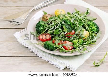 Fresh broccoli salad with cherry tomatoes mix and arugula.Selective focus - stock photo