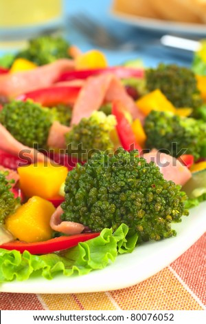 Fresh broccoli salad with lettuce, bell pepper, ham, mango and pomegranate (Selective Focus, Focus on the broccoli floret in the front)