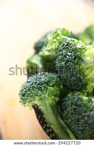 Fresh broccoli spears, washed in a steamer basket on a cutting board - stock photo