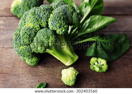 Fresh broccoli with spinach on wooden table close up - stock photo