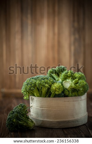 Fresh brocoli florets in a basket on a wooden background